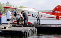 A camper is attended to by ambulance staff after arriving Thursday, July 21, 2016 in Ely, Minn., by floatplane from the Boundary Waters Canoe Area Wilderness after being injured following a severe storm that knocked trees down on Basswood Lake. The injured party received non-life threatening injuries and was treated at the Ely-Bloomenson Community Hospital.  A boy and a woman camping with a Boy Scouts adventure program were killed and two other campers were injured when severe storms swept through a northern Minnesota forest, the leader of the program said Thursday. (AP Photo/Ely Echo Newspaper, Hailey Worth)