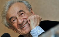 Elie Wiesel smiles during a news conference in Budapest, Hungary. Wiesel, the Nobel laureate and Holocaust survivor has died.  His death was announced Saturday, July 2, 2016  by Israel's Yad Vashem Holocaust Memorial.  (AP Photo/Bela Szandelszky, file)
