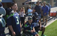 Seahawks WR Doug Baldwin visits with Jesse Bailey (l) and Steven Snider during their Make-A-Wish visit Tuesday at VMAC (Josh Kerns/KIRO Radio)