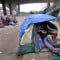 A man lies in a tent with others camped nearby, under and near an overpass in Seattle, which has the third-highest number of homeless people in the U.S. (AP)