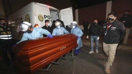 In this photo provided by Peru's Interior Ministry, health workers push the coffin of Abimael Guzma...