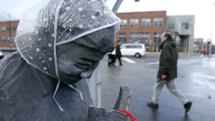 A pedestrian walks past a statue with a rain bonnet on its head in the Fremont neighborhood of Seat...
