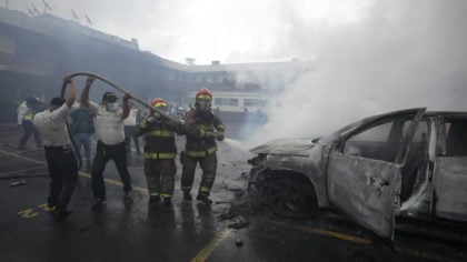 Firefighters and police work together to douse with water a vehicle set on fire by a group of veter...