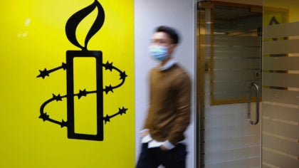 A man walks past the logo of the Amnesty International at its office in Hong Kong Monday, Oct. 25, ...