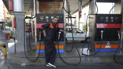 A worker leans against a gasoline pump that has been turned off, at a gas station in Tehran, Iran, ...