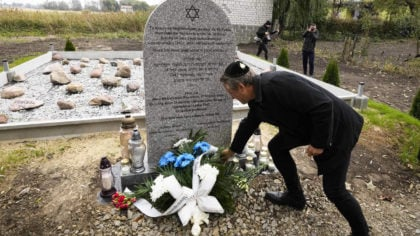 A man lays a candle at a new memorial at a mass grave to some 60 Jews, executed during the Holocaus...