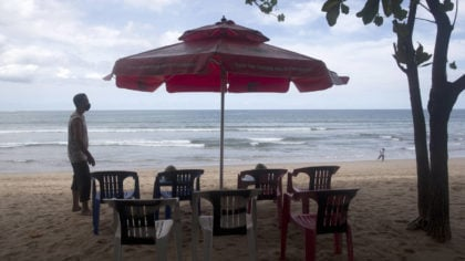 A beach vendor sets chairs as he waits for customers in Kuta beach in Bali, Indonesia, Thursday, Oc...