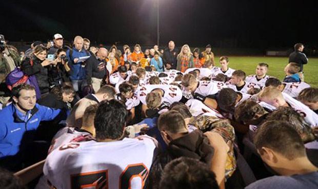 Bremerton football coach Joe Kennedy prays with players on the field. (AP)...